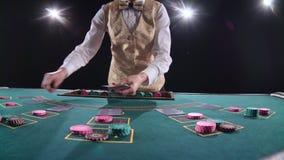 Kasinocroupier verteilt Karten auf die Pokertischplatte unter Verwendung der geschnittenen Karte Schwarzer Hintergrund Helle Leuc stock footage
