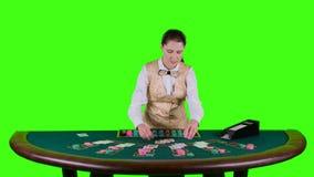 Kasinocroupieranseendet bak det halvcirkelformiga skrivbordet i en vit skjorta fördelar för kort för tabellpoker tre är arkivfilmer