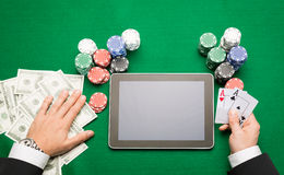 Kasinopokerspieler mit Karten, Tablette und Chips Stockbilder