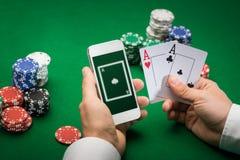 Kasinospelare med kort, smartphonen och chiper Arkivbild