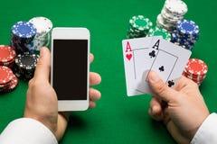 Kasinospieler mit Karten, Smartphone und Chips Lizenzfreies Stockfoto