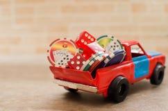 Kasinotecken och tärning på en röd leksakbil Arkivbild