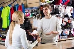 Kasjera pomaga klient przy wynagrodzenia biurkiem zdjęcie royalty free