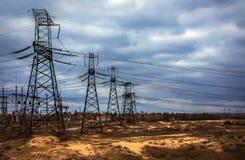 Kaskad av kraftledningar elektricitetsfördelningsstation i stor Royaltyfri Bild