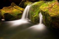 Kaskade auf kleinem Gebirgsstrom Kaltes Kristallwasser fällt über moosige Flusssteine des Basalts in kleines Pool Stockfotografie