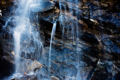 Kaskadenwasser, das weg von den Felsen fließt Stockbilder