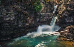 Kaskadenwasserfälle, die in einen Fluss fließen lizenzfreie stockbilder