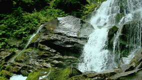 Kaskadenwasserfallspritzen auf Steinen im Wald unter Bergen stock footage