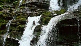 Kaskadenwasserfallspritzen auf Steinen im Wald unter Bergen Langsame Bewegung stock video
