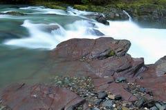 Kaskadierenweißes Wasser- und Flussuferfelsen des flusses Stockfotografie