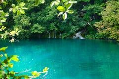 Kaskadowa siklawa i jezioro z turkus wodą Fotografia Stock