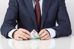 Kassör i bank` s räcker att räkna eurosedlar på tabellen Royaltyfri Fotografi