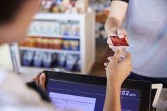 Kassörska Accepts Card Payment från kund i matvaruaffär Arkivfoton
