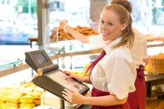 Kassörskan i bagare shoppar att posera med kassaapparaten Arkivbild