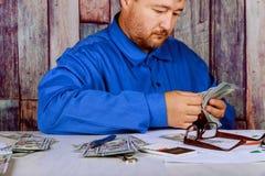 Kassa i handmannen som r?knar pengardollar i man& x27; s r?cker en man i aff?rskl?der med dollar arkivbild