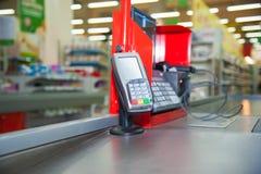 Kassa med betalningterminalen i supermarket Arkivbild