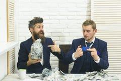 Kassa utfärdar begrepp Affärspartners affärsmän på möte i regeringsställning Chef med skägget och kollega med kruset av arkivfoto
