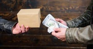 Kassapengar och ask med förbjudet godsutbyte olagligt avtalsbegrepp Hand för pengarkassa in av den brottsliga mannen E royaltyfri fotografi