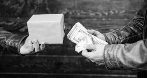 Kassapengar och ask med förbjudet godsutbyte olagligt avtalsbegrepp Hand för pengarkassa in av den brottsliga mannen E arkivbild