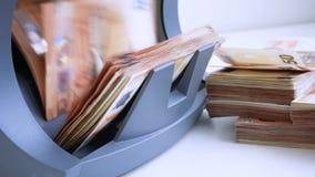 Kassapengarräknaren och avkännaren av sedlar för räkningen av anmärkningar och beslutsamhet av fejkar euro 50 och 20 arkivfilmer