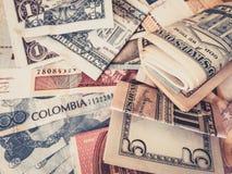 KassapengarUS dollar och colombianska Pesos - royaltyfri bild