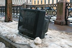 Kasserad TV på granitinvallningen av floden Royaltyfri Bild