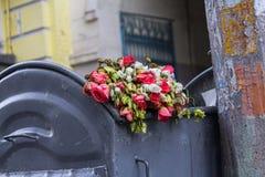 Kasserade blommor som ligger i soptunnan royaltyfri foto
