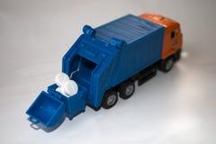 Kasserade piller väljer upp en leksakavfallbil arkivbild