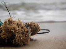 Kasserat fisknät och rep på stranden royaltyfri fotografi
