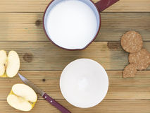 Kasserolle mit heißer Milch und der Schüssel zu frühstücken lizenzfreie stockbilder