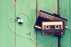 Kassett och gammal bandspelare över träbakgrund retro filter Royaltyfria Foton