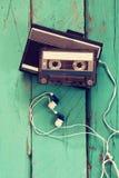 Kassett och gammal bandspelare över träbakgrund retro filter Royaltyfri Foto
