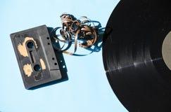 Kassett- och vinylrekord på en kulör bakgrund arkivfoton