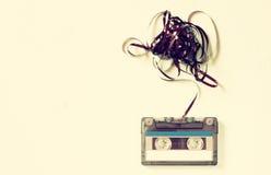 Kassettband över trätabellen med det tilltrasslade bandet Top beskådar retro filter Royaltyfria Foton