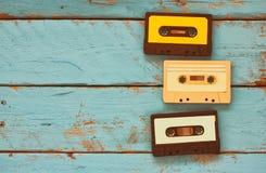 Kassetten über blauem strukturiertem Holztisch Beschneidungspfad eingeschlossen Retro- Filter Lizenzfreie Stockbilder