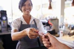 Kassier Accepts Card Payment van Klant in Delicatessen stock foto's