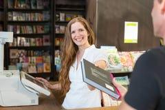 Kassierer in der Buchhandlung, die einen Kunden oder einen Kunden dient stockfotos