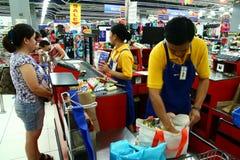 Kassiers en bagger jongens in een kruidenierswinkelopslag in de Filippijnen Stock Fotografie