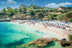 Kassiopi Beach, Corfu Island, Greece. Sunbeds and parasols (sun umbrella) on the beach. Tourists relaxing on beautiful beach of Kasiopi in the north area of Stock Photo