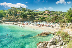 Kassiopi Beach, Corfu Island, Greece. Sunbeds and parasols (sun umbrella) on the beach. Tourists relaxing on beautiful beach of Kassiopi in the north area of Stock Image