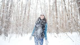Kast för ung kvinna snöar upp med ett trevligt leende i vinterskogen lager videofilmer