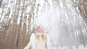 Kast för ung kvinna snöar upp med ett trevligt leende i vinterskogen stock video