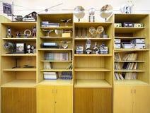 Kast met fysieke apparaten en boeken in s royalty-vrije stock fotografie