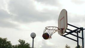 Kasta bollen in i det utomhus- basketbeslaget Basketspelare som kastar bollen i cirkel på sportjordning skrivande in m?l f?r boll arkivfilmer