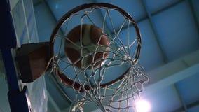 Kasta en boll in i basketcirkeln mot bakgrunden av strålkastare långsam rörelse arkivfilmer