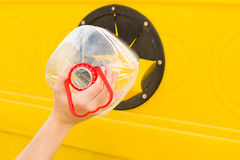 Kasta en flaska in i återvinningbehållaren Royaltyfria Bilder