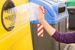 Kasta en flaska in i återvinningbehållaren Arkivbilder