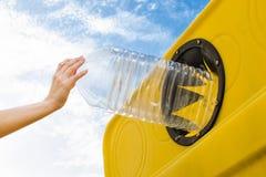 Kasta en flaska in i återvinningbehållaren Arkivbild