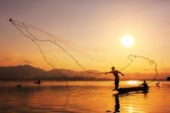 kasta för fisknätsolnedgång Arkivfoto