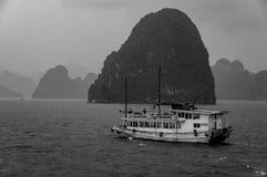 Kasta fartyget seglar in i regnet i mummel den långa fjärden, Vietnam, med regn i förgrunden och mist i avståndet arkivbilder